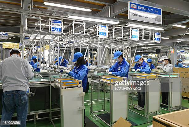 Workers assemble 110w direct pipe LED lights on a production line at Japan's Hitachi Appliances Inc Taga Works in Hitachi about 150 km east of Tokyo...
