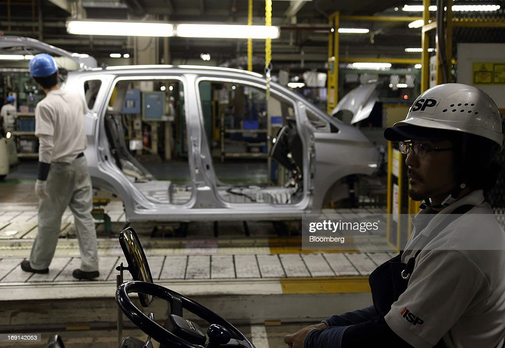 Workers assemble a minicar which will be sold as the Nissan DAYZ by Nissan Motor Co. and Mitsubishi eK Wagon by Mitsubishi Motors Corp. on the production line of the Mitsubishi Motors Mizushima plant in Kurashiki City, Okayama Prefecture, Japan, on Monday, May 20, 2013. Nissan will start selling the first minicar it jointly developed with Mitsubishi Motors in Japan next month amid increasing demand from the nation's consumers for smaller and cheaper vehicles. Photographer: Tomohiro Ohsumi/Bloomberg via Getty Images