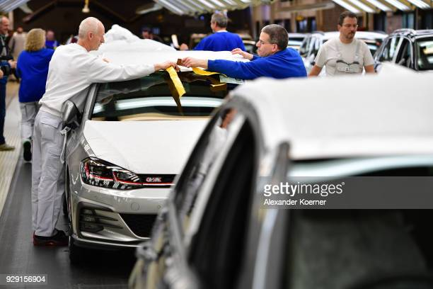 Workers assemble a Volkswagen Golf GTI car at the Volkswagen factory on March 8 2018 in Wolfsburg Germany US President Donald Trump has threatened to...