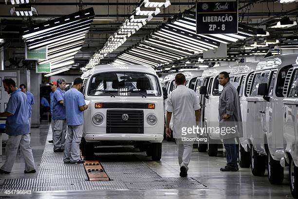 Workers assemble an engine for a Volkswagen AG camper van or microbus known as a 'Kombi' in Brazil on the production line at Volkswagen's Anchieta...