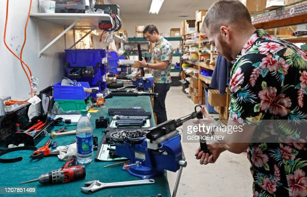 Workers assemble AR15 rifles at Delta Team Tactical in Orem Utah on March 20 2020 Gun stores in the US are reporting a surge in sales of firearms as...