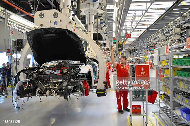 Workers assemble at Ferrari factory on May 8 2013 in Maranello Italy Ferrari plans to limit the production belowe 7000 units to maintain the...