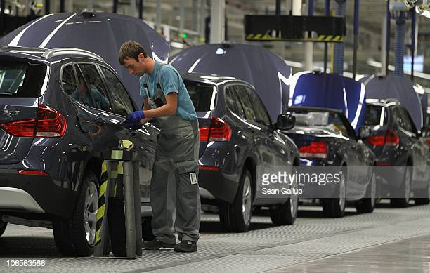 Workers assemble BMW cars at the BMW auto assembly plant on November 5 2010 in Leipzig Germany Earlier in the day German Chancellor Angela Merkel and...