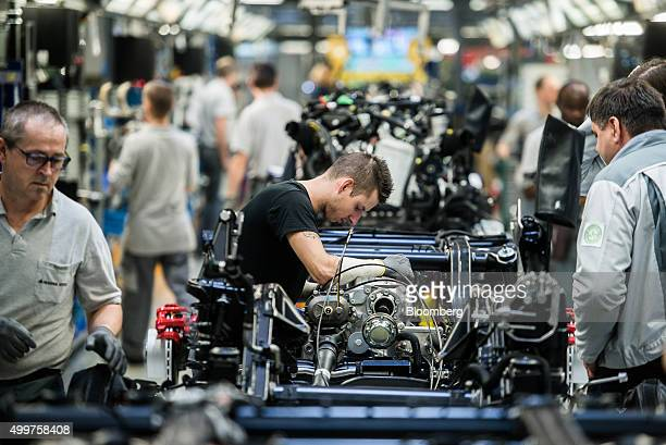 Workers assemble chassis for MercedesBenz AG GClass automobiles on the production line at the Magna International Inc plant in Graz Austria on...
