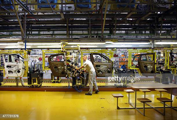 Workers assemble door panels for new Renault Smart For Four automobiles as they pass along the production line at the Renault Revoz dd plant a unit...