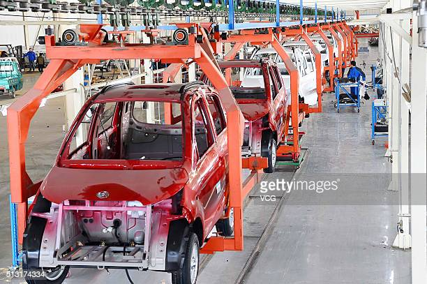 Workers assemble electric automobiles at a workshop in Qingzhou City on March 1 2016 in Weifang Shandong Province of China The manufacturing sector...