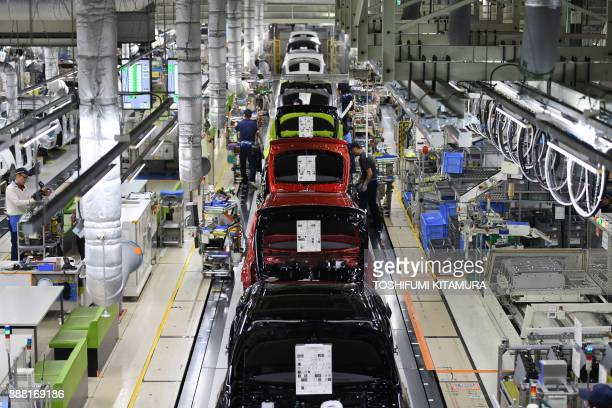 Workers assemble fourth generation Toyota Prius cars on the production line at the company's Tsutsumi assembly plant in Toyota City, Aichi prefecture...