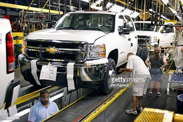 Workers assemble General Motors trucks on the assembly line at the GM Flint Assembly plant July 18 2011 in Flint Michigan GM announced they will be...