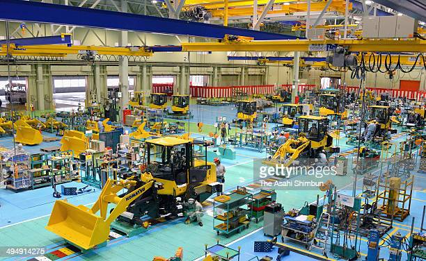 Workers assemble heavy machines at its Awazu Facotry on May 30 2014 in Komatsu Ishikawa Japan The new factory has shortened the production line...