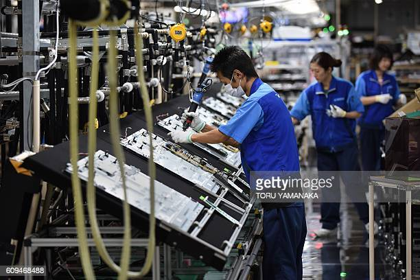 Workers assemble LCD 4K televisions on an assembly line at the Utsunomiya Plant of Japan's electronics giant Panasonic in Utsunomiya 100 kilometres...