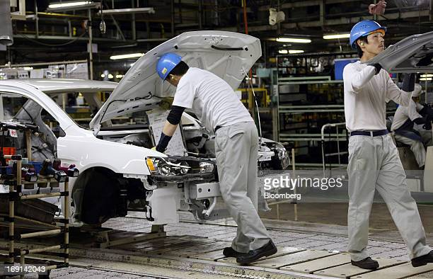 Workers assemble Mitsubishi Motors Corp vehicles on the production line of the Mitsubishi Motors Mizushima plant in Kurashiki City Okayama Prefecture...