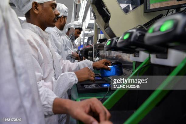 Workers assemble mobile phones at an Indian Lava phone manufacturer factory in Noida on August 22 2019