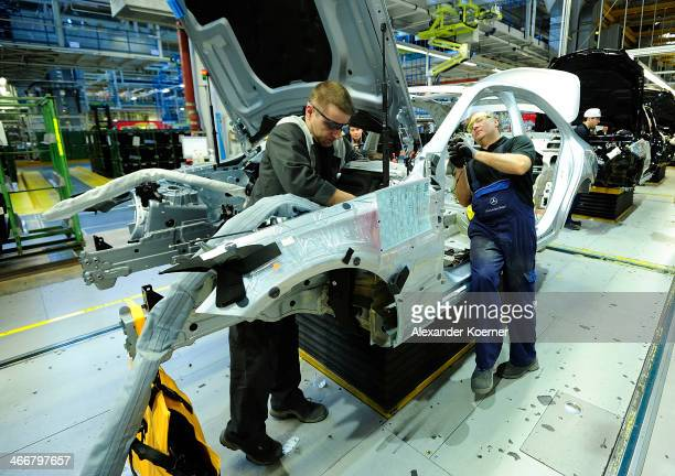 Workers assemble new CClass automobiles on the assembly line at the MercedesBenz plant of Daimler AG on February 04 2014 in Bremen Germany...