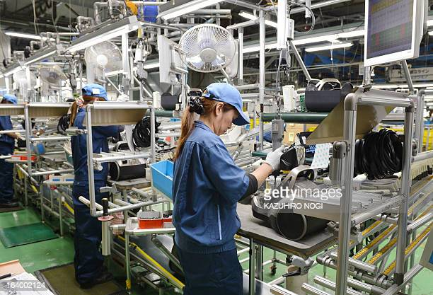 Workers assemble new vacuum cleaners on a production line at Japan's Hitachi Appliances Inc Taga Works in Hitachi about 150km east of Tokyo on March...