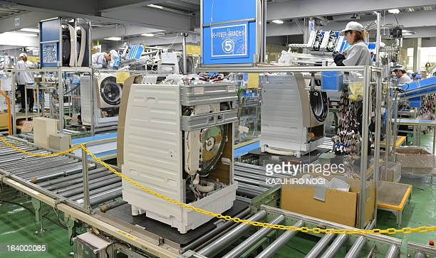 Workers assemble new washing machines on a production line at Japan's Hitachi Appliances Inc Taga Works in Hitachi about 150 km east of Tokyo on...