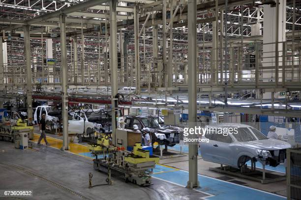 Workers assemble Nissan Motor Co Navara pickup trucks on an assembly line at the company's plant in Samut Prakan Thailand on Tuesday April 25 2017...