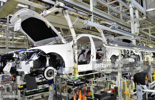 Workers assemble on the production line at the Toyota Motor Co Motomachi factory on July 30, 2018 in Toyota, Aichi, Japan.