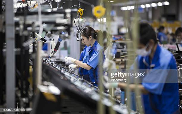 Workers assemble Panasonic Corp Viera 4K liquid crystal display televisions on the production line of the company's Manufacturing Innovation Center...