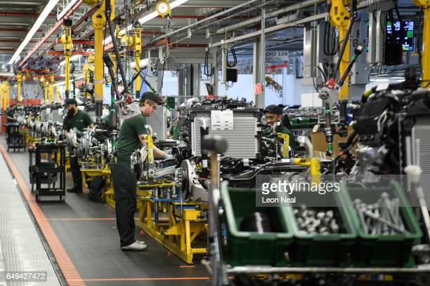 Workers assemble parts of the chassis during an early stage of production at the Jaguar Land Rover factory on March 1 2017 in Solihull England The...