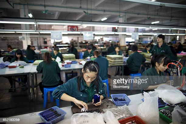 Workers assemble pens at the AW FaberCastell Stationery Co factory in Guangzhou Guangdong province China on Tuesday Nov 26 2013 The Purchasing...