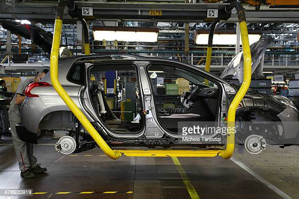 Workers assemble Peugeot 2008 SUVs at the PSA Peugeot Citroen assembly plant on March 14 2014 in Mulhouse France Chinese automaker Dongfeng is...