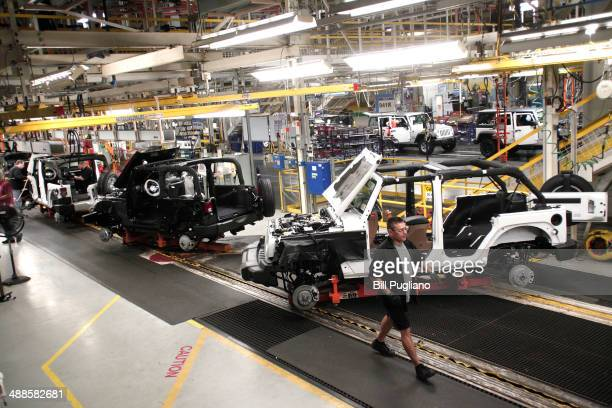 Workers assemble the 2014 Jeep Wrangler at the Chrysler Toledo North Assembly Plant Jeep May 7 2014 in Toledo Ohio iat Chrysler Automobiles announced...