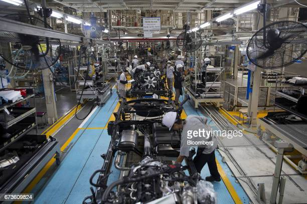 Workers assemble the chassis and powertrains of Nissan Motor Co Navara pickup trucks on an assembly line at the company's plant in Samut Prakan...