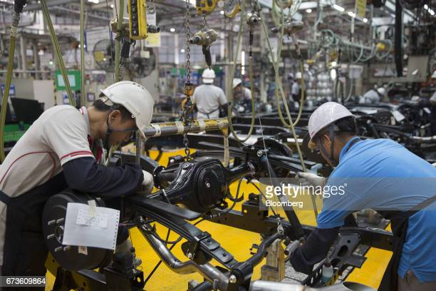 Workers assemble the chassis of a Nissan Motor Co Navara pickup truck on an assembly line at the company's plant in Samut Prakan Thailand on Tuesday...