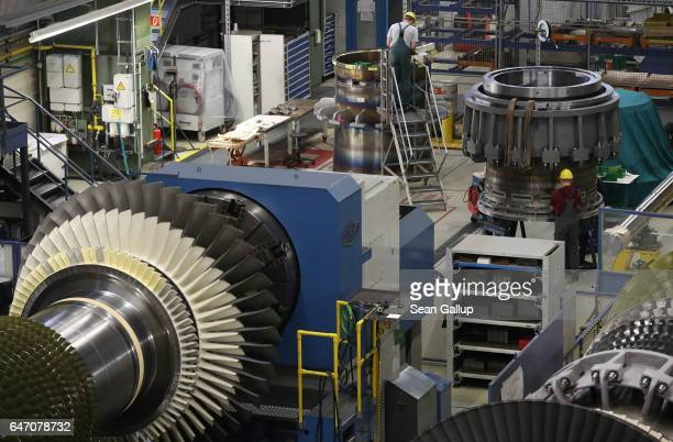 Workers assemble turbine components at the Siemens gas turbine factory on March 2 2017 in Berlin Germany Germany's number of unemployed fell by 15000...