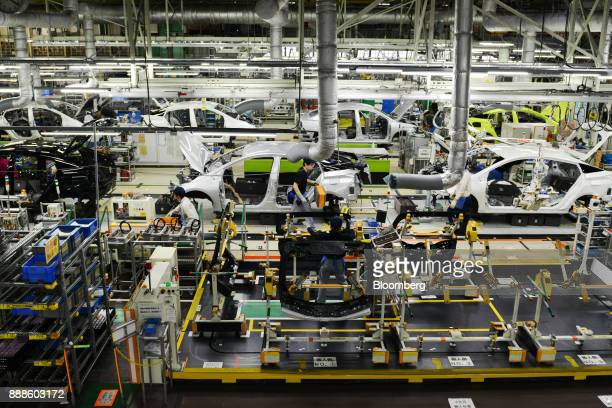 Workers assemble vehicles on the Prius hybrid and Priyus plug-in hybrid vehicle production line of the Toyota Motor Corp. Tsutsumi plant in Toyota...