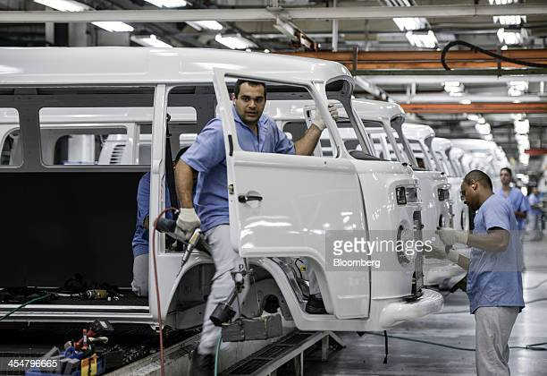 Workers assemble Volkswagen AG camper vans or microbuses known as 'Kombis' in Brazil on the production line at Volkswagen's Anchieta plant in Sao...