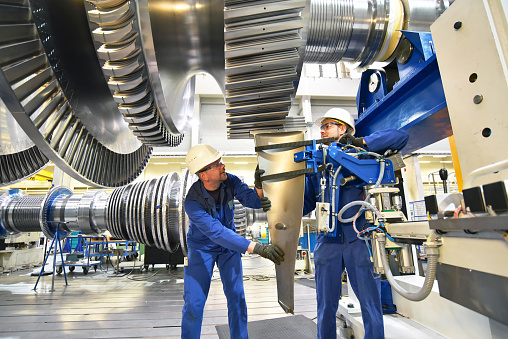 workers assembling and constructing gas turbines in a modern industrial factory 1056710182