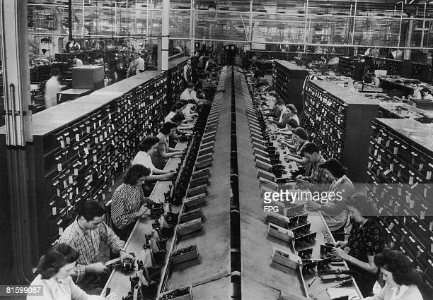 Workers assembling control units for tanks and aircraft in a US factory circa 1943