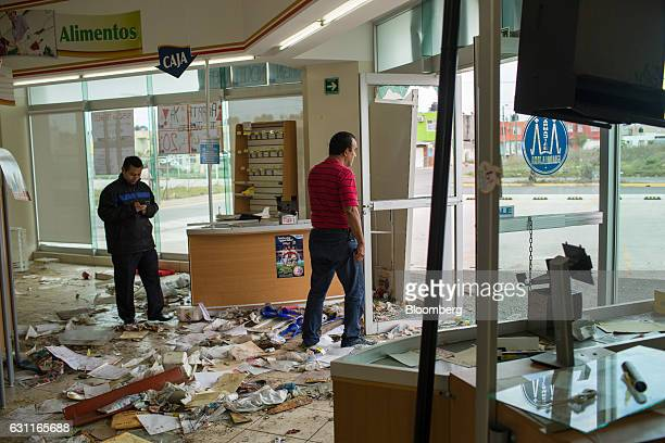 Workers assess the damage at the Guadalajara Pharmacy after looting in Veracruz City Mexico on Saturday Jan 7 2017 Mexico's National Association Of...