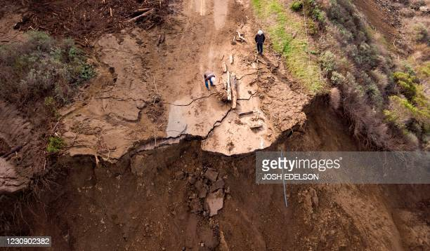 Workers assess the scene where a section of Highway 1 collapsed into the Pacific Ocean near Big Sur, California on January 31, 2021. - Heavy rains...