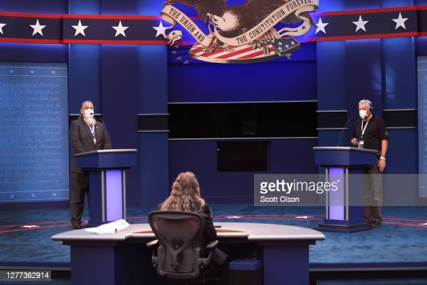Workers assume the positions of President Donald Trump, Democratic presidential nominee Joe Biden and moderator Chris Wallace as they prepare the...