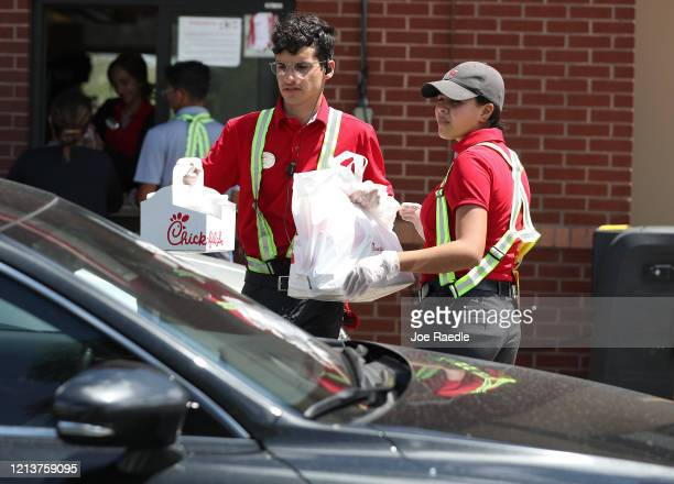Workers at a ChickfilA deliver meals to customers in their vehicles at the driveup window after the restaurant closed its indoor seating in an effort...