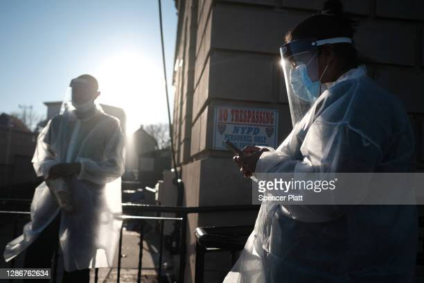 Workers at a COVID-19 testing location take a break in the Staten Island neighborhood of Tottenville on November 20, 2020 in New York City. The...