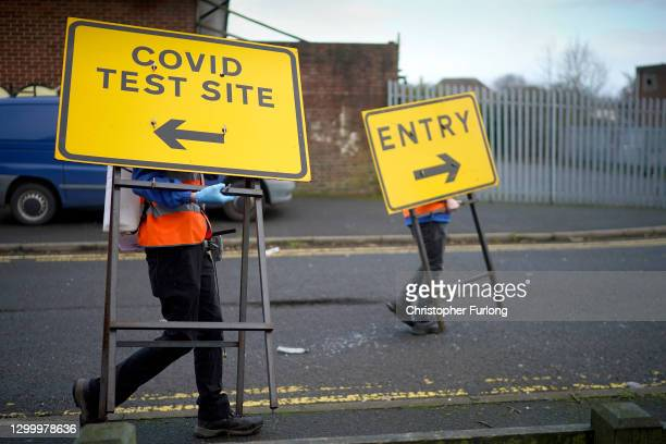 Workers at a drive in testing station at Walsall Arena and Arts Centre remove direction signs after the first day of covid-19 testing to track down a...