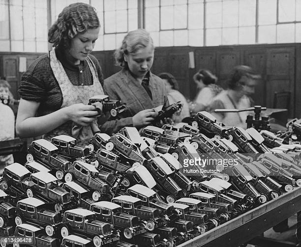 Workers at a toy factory polish small toy cars for the Christmas rush