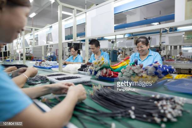 workers at an electronics factory in dongguan, china - electronics stock pictures, royalty-free photos & images