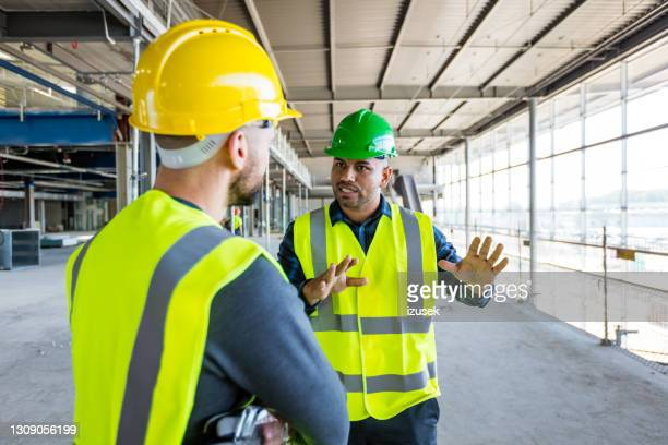 workers at an indoor construction site - izusek stock pictures, royalty-free photos & images