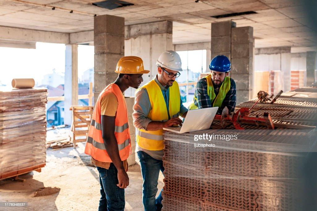 Werknemers op bouwwerk plaats binnen gebouw : Stockfoto