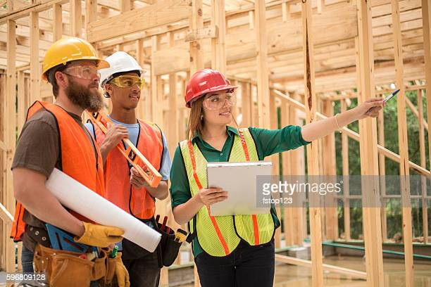 workers at construction job site inside framed building. - real estate developer stock pictures, royalty-free photos & images