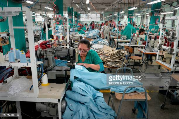 Workers at Kinross Clothing manufacturers in Maitland sew men's trousers on October 19 in Cape Town South Africa is fighting to revive its frayed...