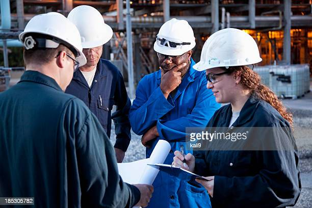 workers at manufacturing plant - black jumpsuit stock photos and pictures