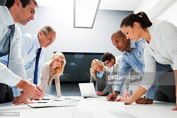 Workers at office meeting standing to see reports