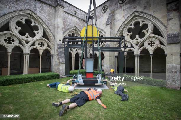 Workers at Salisbury Cathedral help install Dame Barbara Hepworths sculpture Construction Homage to Piet Mondrian into place in its new home in the...