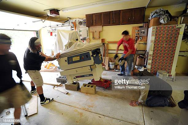 Workers at Stockton Manor raise a table saw from possible flood waters in preparation for Hurricane Sandy October 27, 2012 in Cape May, New Jersey....