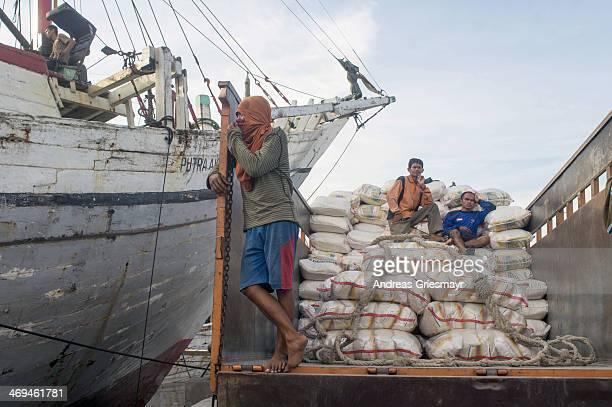 Workers at Sundar Kelapa port in Jakarta unloading cargo from a wooden ship onto a truck